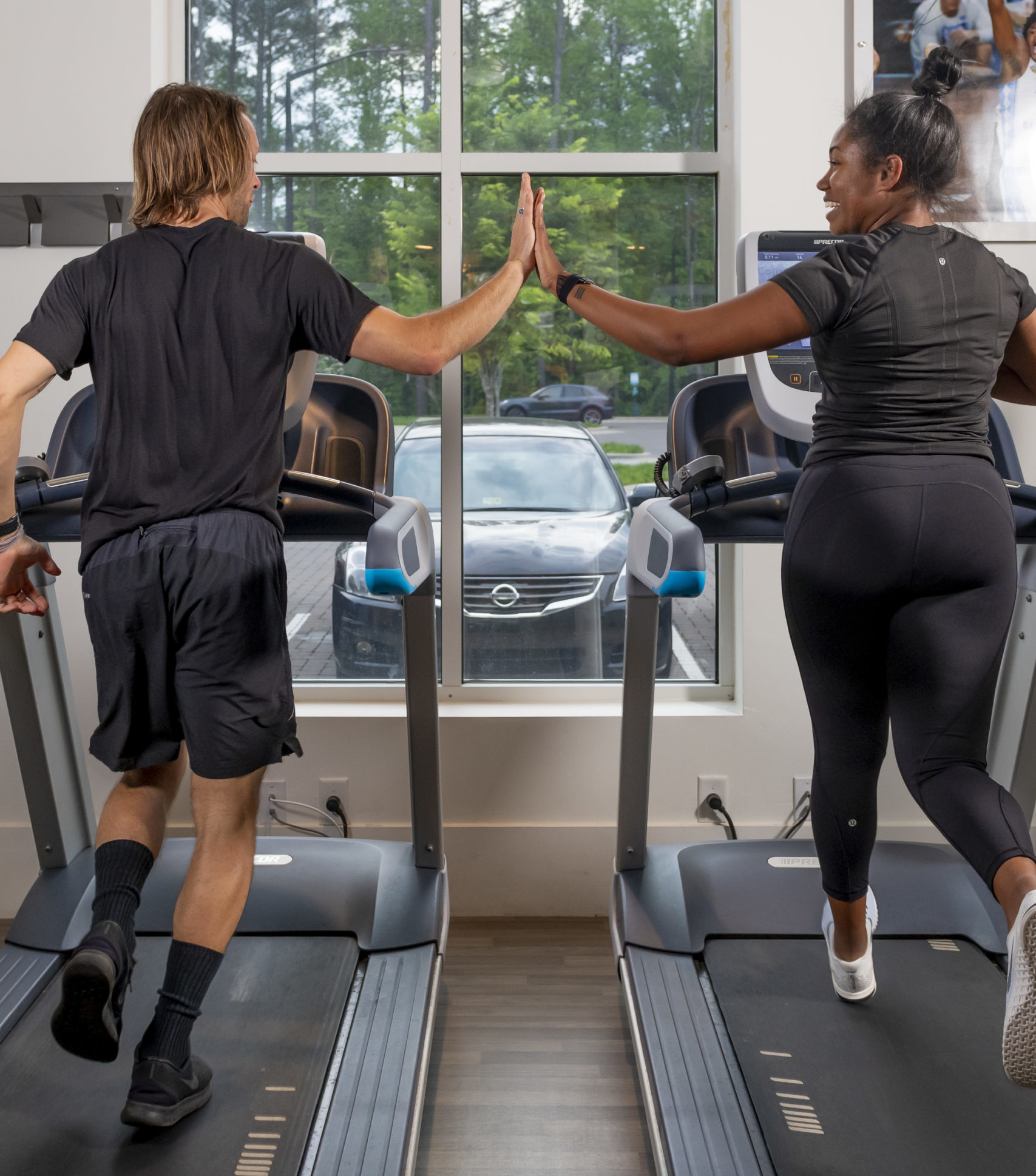 friends high-fiving on treadmills while they run and work out at evolve