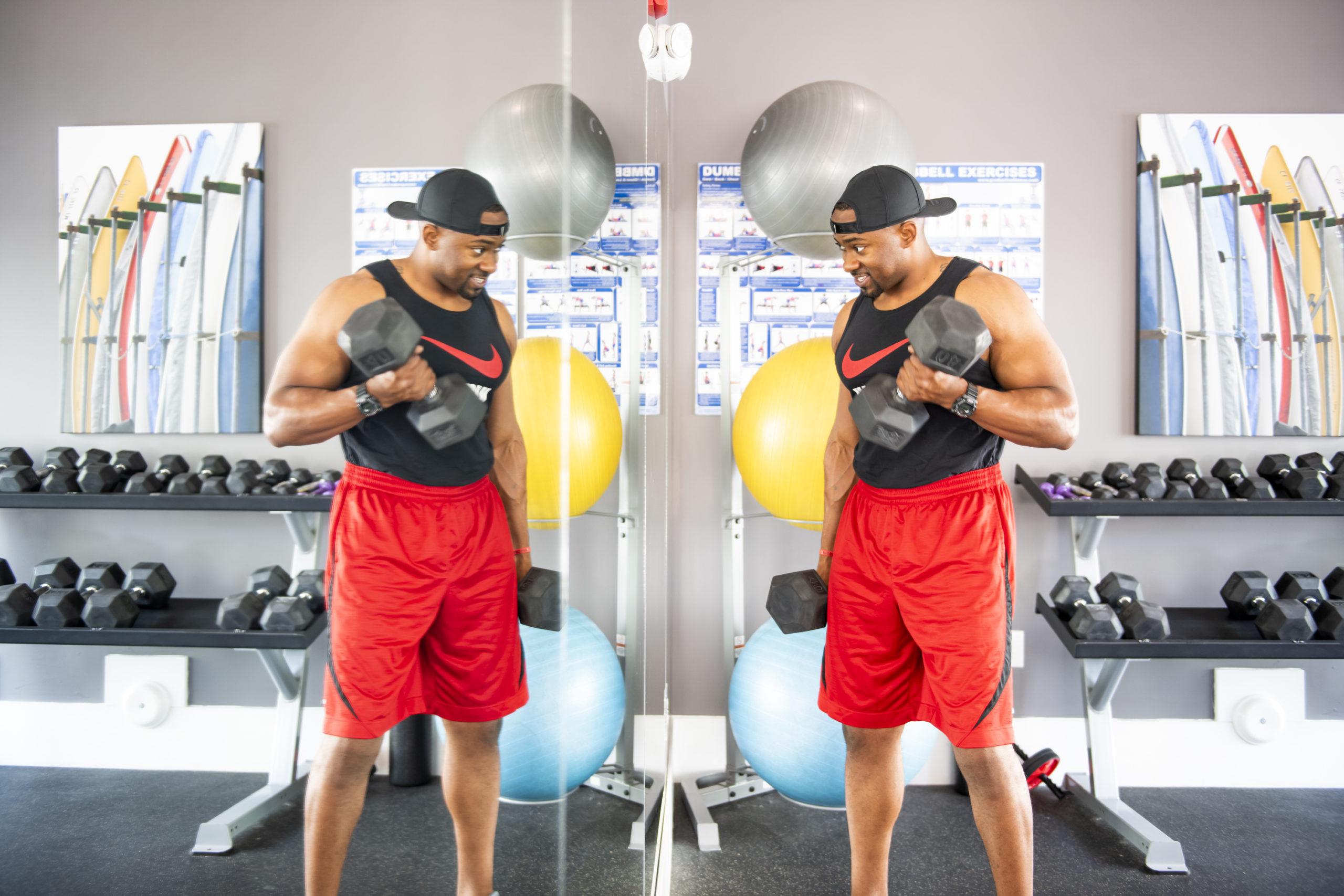 guy using dumbbells in evolve fitness center new workout