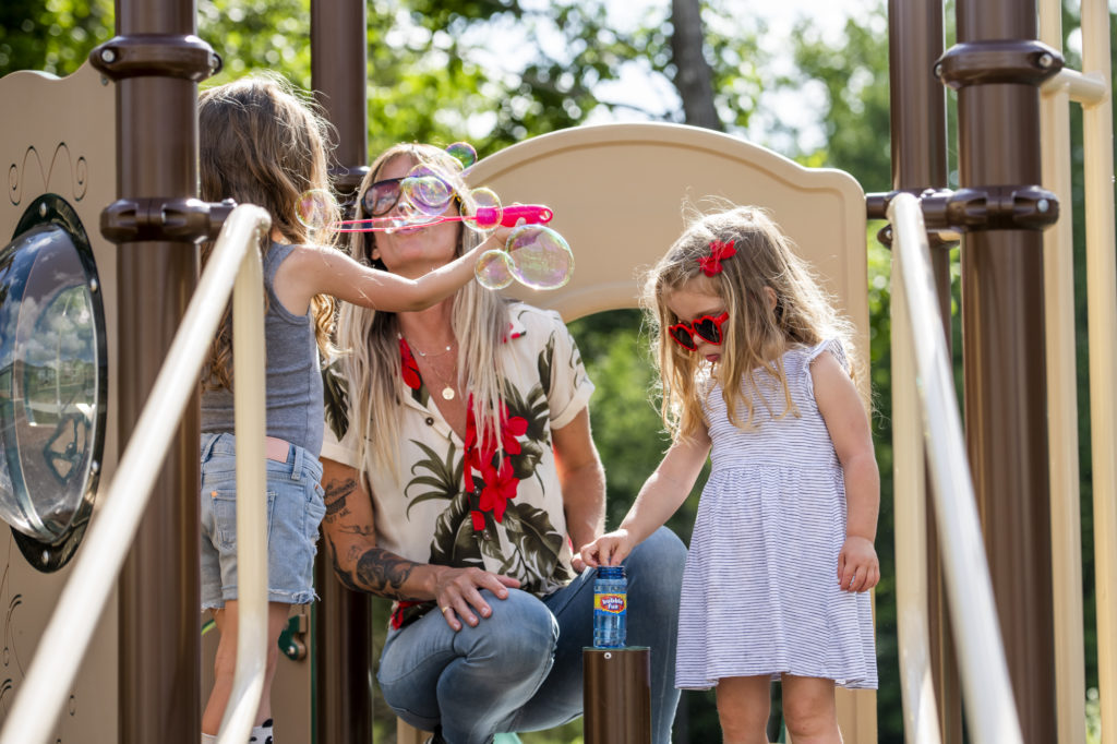 woman with kids blowing bubbles on playground