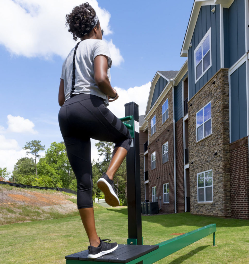 girl on outdoor fitness equipment at evolve community